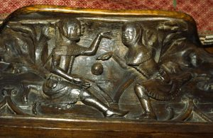Wood carving of an early football game
