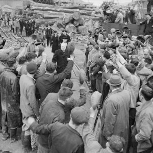 Winston Churchill is cheered by workers during a visit to bomb-damaged Plymouth on 2 May 1941. The Prime Minister was accompanied by Lady Nancy Astor, Lord Mayoress of Plymouth, behind Churchill.