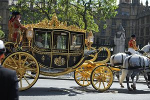 The Queen arrives at Westminster in a black and gold horse-drawn coach
