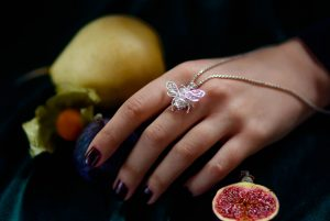 Silver bee pendant draped on a model's hand